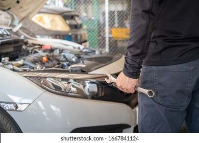 Professional mechanic man holding spanner tool for repair and maintenance car in garage