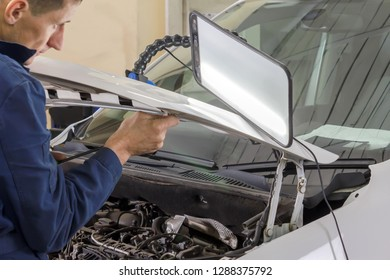 Professional mechanic removes dents on the car body