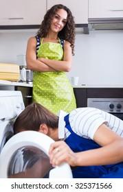 Professional mechanic repairing washing machine of happy female client
