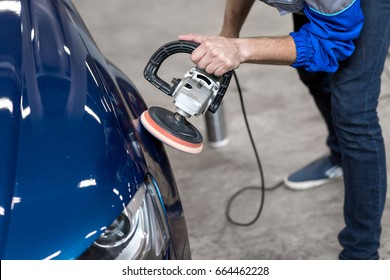 professional mechanic using a power buffer machine for cleaning the body of a car from scratches.