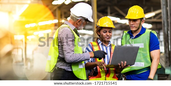 Professional Mechanical Engineer team Working on Personal Computer at Metal lathe industrial manufacturing factory. Engineer Operating  lathe Machinery. Product quality Inspection