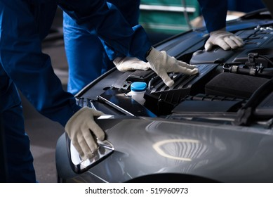 Professional mechanics chacking car engine
