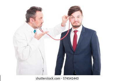 Professional medic cheking  head of insane lawyer for brain problems isolated on white background