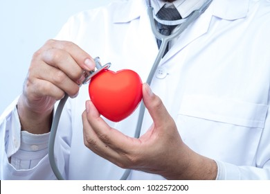 Professional medical doctor holding a stethoscope check up on a red heart ball. Concept of health care.