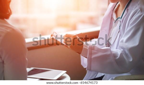 白衣を着た専門医のインタビューカウンセリング女性患者:診察時に患者図に書き込む医師:病院/診療所のプロ意識