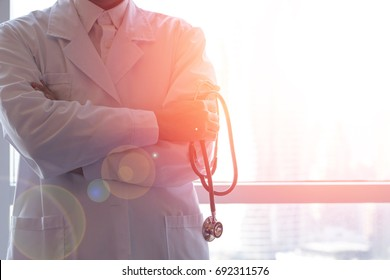 Professional medical physician doctor in white uniform gown coat hand holding stethoscope in clinic hospital.Medical/ healthcare/ technology concept