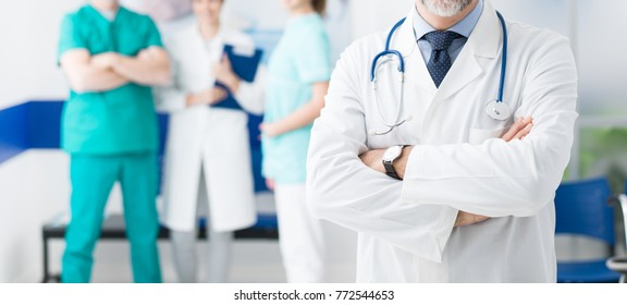 Professional medical team working at the hospital and confident doctor posing with arms crossed on the foreground