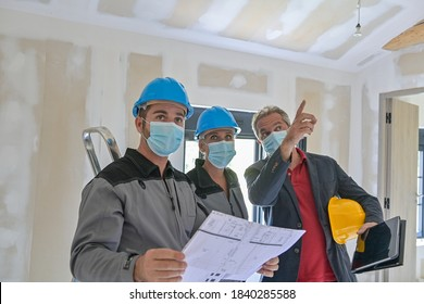 Professional meeting on a construction site between the architect and the craftsmen who wear a protective mask against covid-19