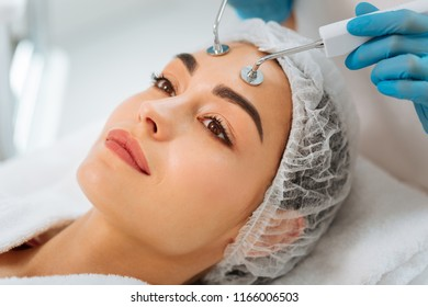 Professional microcurrent therapy. Portrait of a nice young woman having MCT in the beauty salon