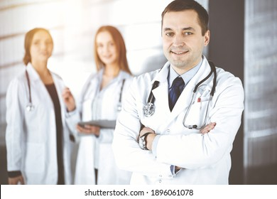 Professional middle aged doctor with a stethoscope and crossed arms at work, standing together with his female colleagues in a sunny clinic. Perfect medical service in a hospital. Medicine and