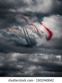 Professional military pilots flying their supersonic jets in attack formation at the air show while leaving colorful smoke traces on the cloudy sky.