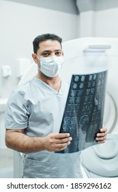 Professional mixed-race radiologist in mask and uniform holding x-ray image of patient head against environment of medical office
