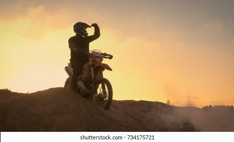 Professional Motocross Biker Spectacularly Stands on the Off-Road Dune on his Enduro Motorcycle. Looks Afar on the Whole Track.