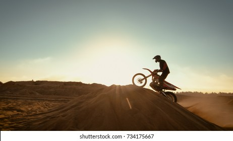 Professional Motocross Motorcycle Rider Jumping Over the Dune and Further Down the Off-Road Track. Shot on Deserted Quarry while Sun is Setting.