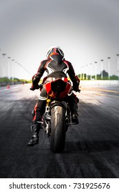 Professional motorcycle biker in leather suit and safety helmet ready to race on race track.