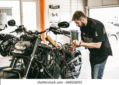 Professional motorcycle mechanic working in bike repair service. Mechanic checking a bike battery level with voltmeter in garage