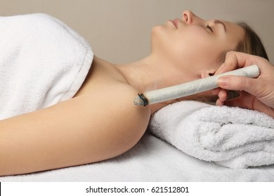 Professional moxa stick in hand of practitioner over woman's body