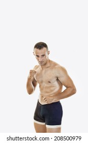 Professional muscular boxer standing in fight pose in naked torso isolated over white background