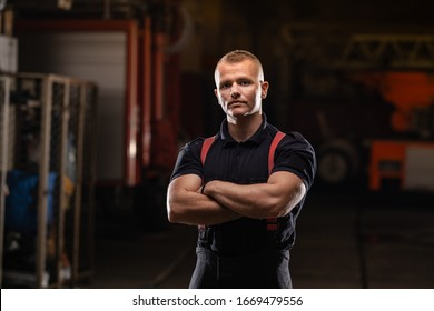 professional muscular firefighter portrait wearing shirt and red throuser suspenders. fire trucks in the background.