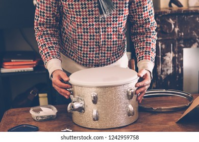 a professional musician is busy to tune a handmade drum