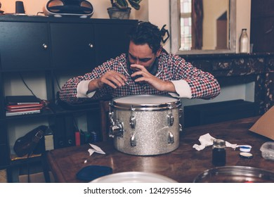 a professional musician is busy tuning a handmade drum