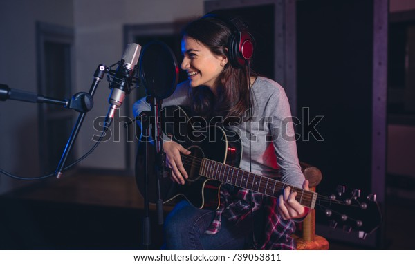 Professional musician recording in studio. Female guitarist sitting in front of microphone and smiling. Singing song for album in recording studio.
