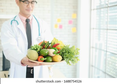 Professional nutritionist asia man holding fresh vegetables in clinic room