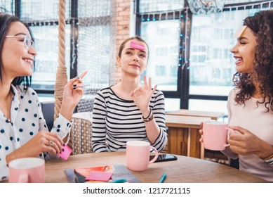 Professional occupation. Nice positive showing the Ok sign while sitting together with her friends