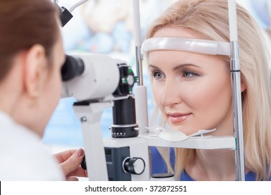 Professional oculist is checking human vision with equipment