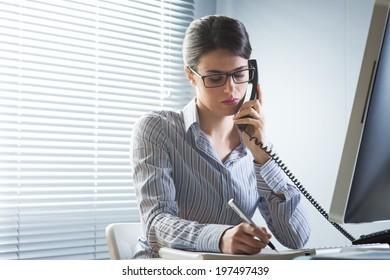 Professional office worker on the phone writing down notes at desk.