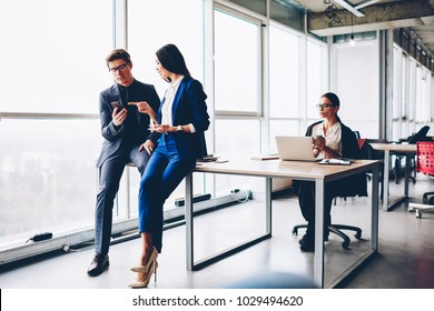 Professional office workers using modern technology for completing successful job projects, male manager showing modern application on smartphone for business while female colleague working on netbook