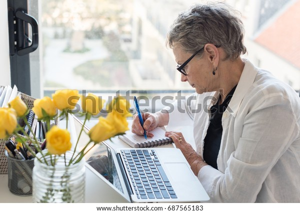 Professional older woman working at desk with computer by a window (selective focus)