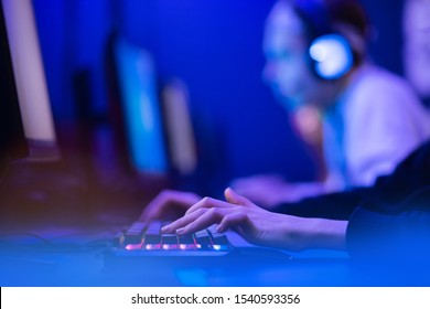 Professional online gamer hand fingers mechanical keyboard in neon color blur background. Soft focus, back view.