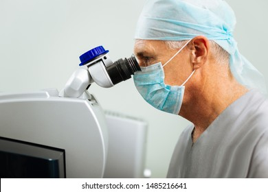 Professional ophthalmologist. Smart serious doctor looking into the microscope while checking his patients eyesight