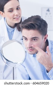 Professional optician and man trying on contact lens