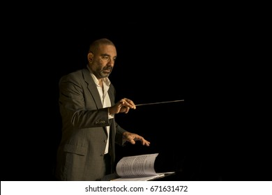 Professional orchestral conductor working, gesturing, on white background