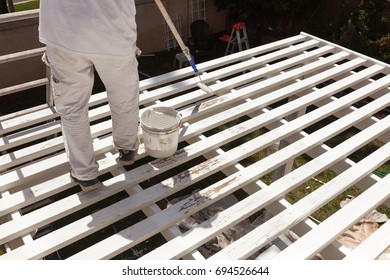 Professional Painter Rolling White Paint Onto The Top of A Home Patio Cover.