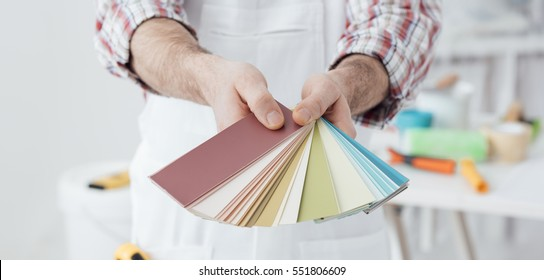 Professional painter showing a set of color swatches, home decoration and renovation concept