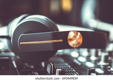 Professional party dj headphones.Black headset on sound mixing controller.Audio equipment for disc jockey.Listen to the music.Pro setup for concert performance