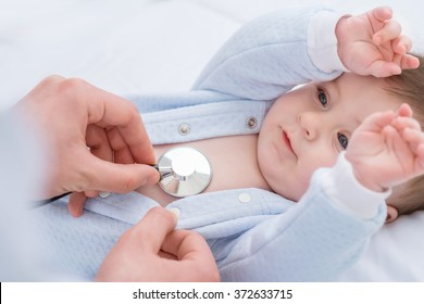 Professional pediatrician examining infant