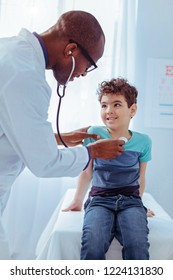 Professional pediatrician. Joyful positive doctor smiling while enjoying working with children