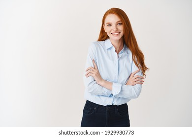 Professional people. Young happy redhead woman smiling at camera, cross arms on chest confident, standing in office blouse over white background