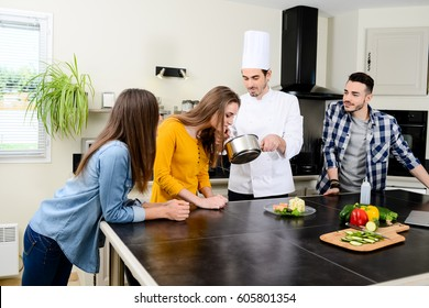 professional personal chef cook in customer's private kitchen house giving a cooking lesson to young people at home