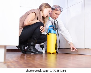 a professional pest control contractor or exterminator squads with the young female customer in the kitchen on the ground and show her problems with mold pests bugs and have a chemical container