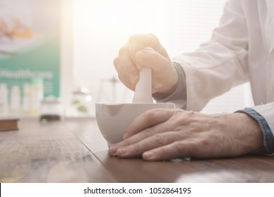Professional pharmacist grinding a medical preparation using a mortar and pestle, pharmacy and medicine concept, hands close up