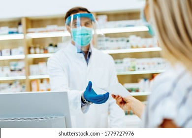 Professional pharmacist with protective mask and face shield on his face  working with customer in modern drugstore.  They are all wearing protective masks on their faces.