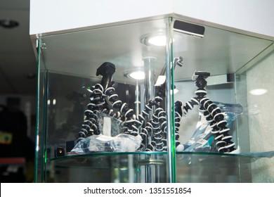 Professional photo equipment store. Showcase with the flexible mini-tripod for camera. Close-up.