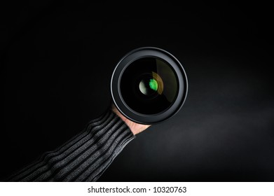 professional photo lens in a man´s hand on black background