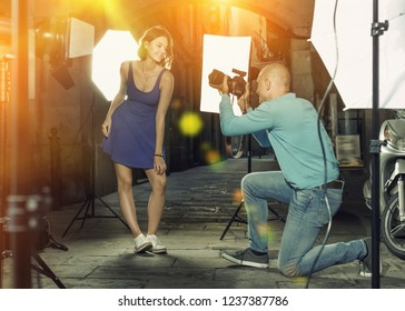 Professional photo shooting outdoors. Attractive glad  beautiful female model posing to photographer on city street