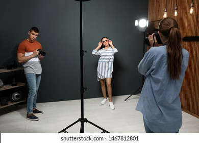 Professional photographer with assistant taking picture of young man in modern studio